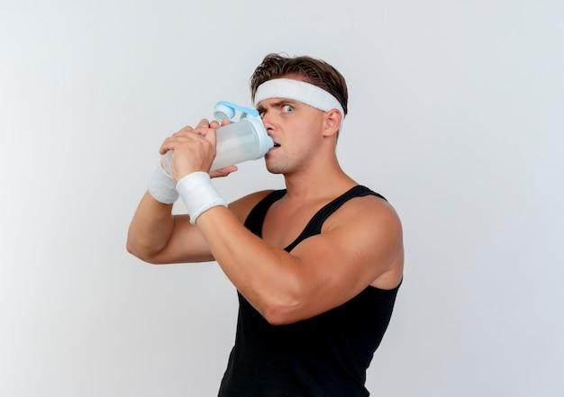 Beeindruckter junger hübscher sportlicher mann, der stirnband und armbänder trinkt, die wasser von der wasserflasche trinken, lokalisiert auf weiß