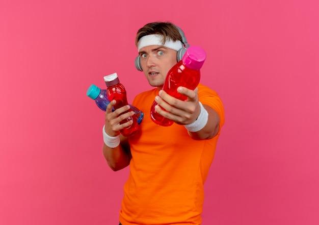 Beeindruckter junger hübscher sportlicher mann, der stirnband und armbänder und kopfhörer trägt, die wasserflaschen halten und ausstrecken, die auf rosa isoliert werden