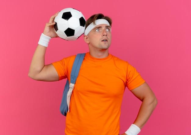 Beeindruckter junger hübscher sportlicher mann, der stirnband und armbänder und rückentasche hält, die fußball hält und kopf mit ihm sucht, der mit hand auf taille auf rosa lokalisiert schaut