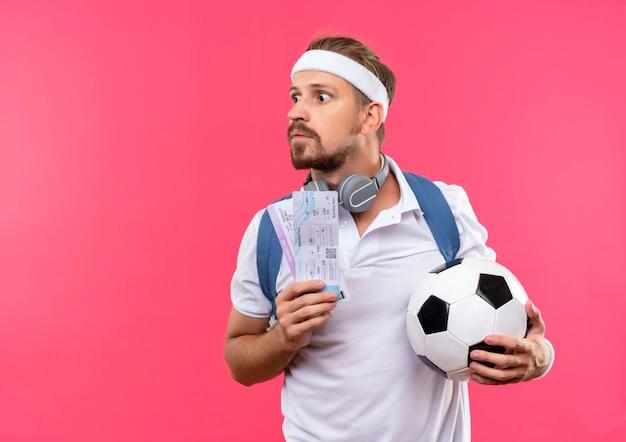 Beeindruckter junger hübscher sportlicher mann, der stirnband und armbänder und rückentasche mit kopfhörern am hals trägt