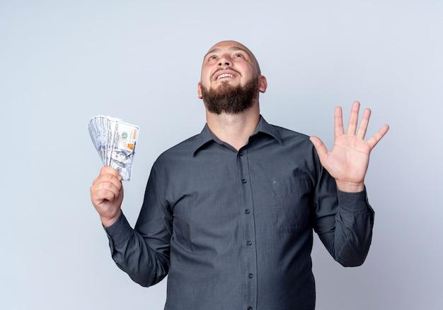 Beeindruckter junger kahlköpfiger callcenter-mann, der geld hält, das leere hand zeigt und isoliert auf schaut