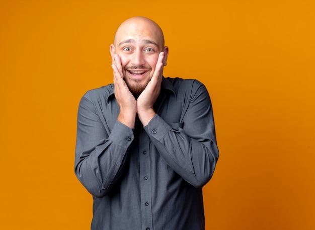 Beeindruckter junger kahlköpfiger callcenter-mann, der hände auf gesicht lokalisiert auf orange mit kopienraum setzt