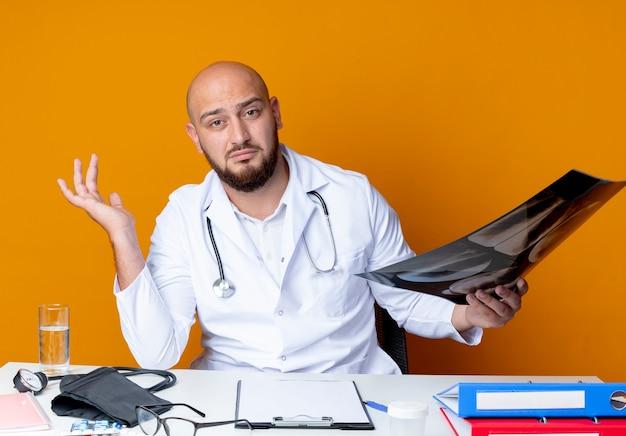 Beeindruckter junger kahlköpfiger männlicher arzt, der medizinische robe und stethoskop trägt und am schreibtisch sitzt sitting