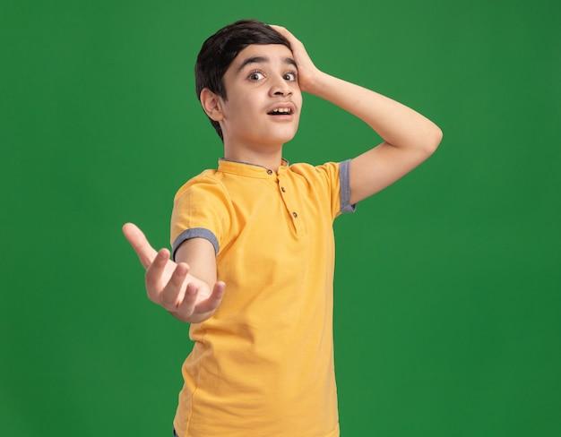 Beeindruckter junger kaukasischer junge, der die hand auf den kopf legt und die hand ausstreckt