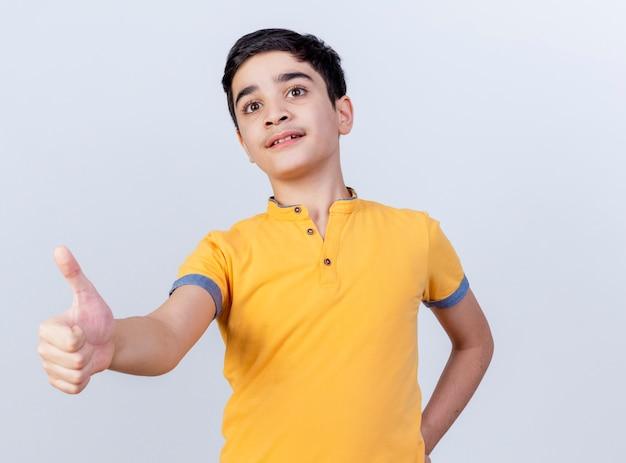 Beeindruckter junger kaukasischer junge, der hand auf taille hält, die gerade zeigt daumen lokalisiert auf weißem hintergrund mit kopienraum