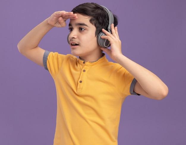 Beeindruckter junger kaukasischer junge, der kopfhörer trägt und greift, die hand auf der stirn hält und seitlich in die ferne schaut