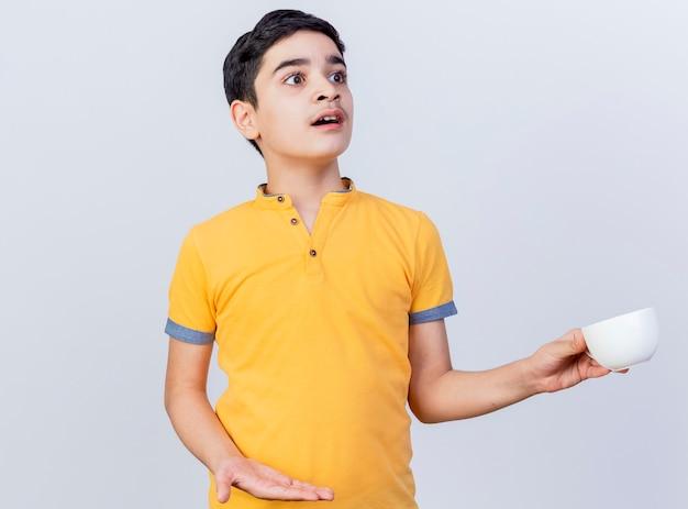 Beeindruckter junger kaukasischer junge, der tasse hält, die leere hand betrachtet, die seite lokalisiert auf weißem hintergrund mit kopienraum betrachtet