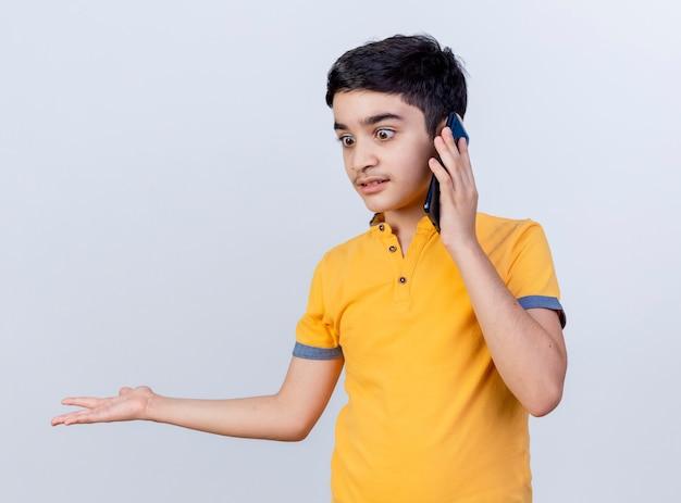 Beeindruckter junger kaukasischer junge, der unten schaut und am telefon spricht, das leere hand lokalisiert auf weißem hintergrund zeigt