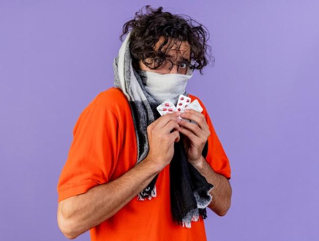 Beeindruckter junger kaukasischer kranker mann, der brille und schal hält, die medizinische pillen betrachten, die kamera lokalisiert auf lila hintergrund mit kopienraum betrachten