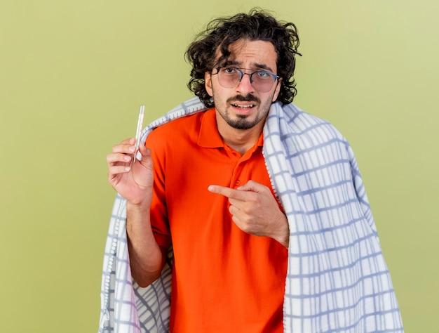 Beeindruckter junger kaukasischer kranker mann, der die brille trägt, die im karierten halten eingewickelt ist und auf thermometer zeigt, das kamera lokalisiert auf olivgrünem hintergrund betrachtet