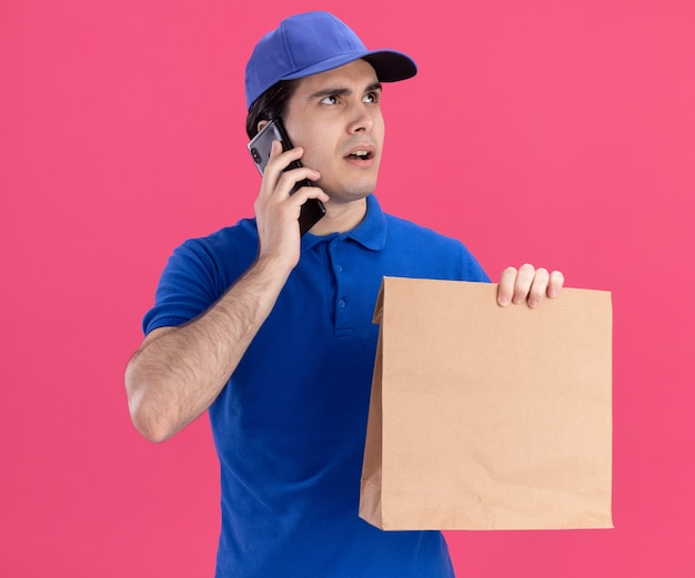 Beeindruckter junger kaukasischer lieferbote in blauer uniform und mütze mit papierpaket, das am telefon spricht, isoliert auf rosa wand