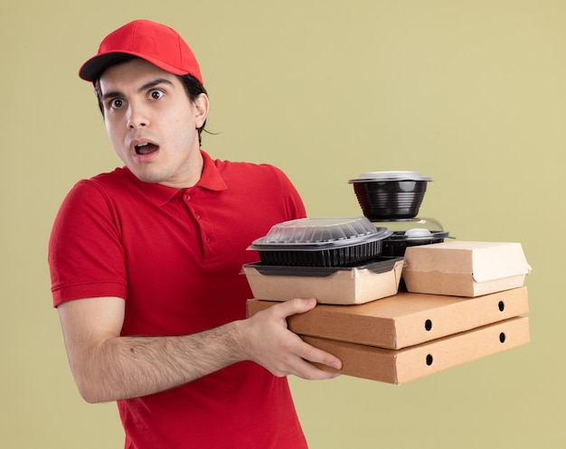 Beeindruckter junger kaukasischer lieferbote in roter uniform und mütze, die pizzapakete mit lebensmittelbehältern und papierverpackungen auf ihnen hält, die auf die seite schauen