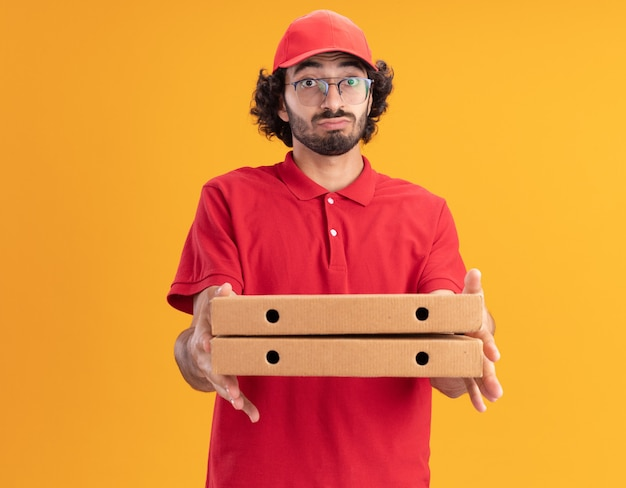 Beeindruckter junger kaukasischer lieferbote in roter uniform und mütze mit pizzapaketen