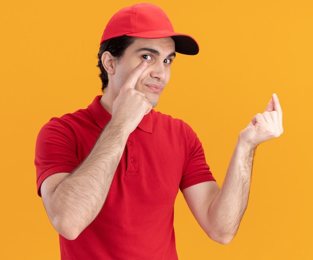 Beeindruckter junger kaukasischer liefermann in blauer uniform und mütze, der eine tippgeste macht, die mit dem finger auf das auge zeigt