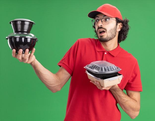 Beeindruckter junger kaukasischer liefermann in roter uniform und mütze mit brille, die lebensmittelverpackungen aus papier und lebensmittelbehälter mit blick auf lebensmittelbehälter hält