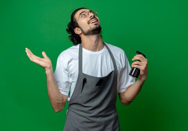 Beeindruckter junger kaukasischer männlicher friseur, der brille und welliges haarband in der uniform hält, die sprühflasche hält, die leere hand zeigt und lokal auf grünem hintergrund schaut