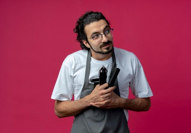 Beeindruckter junger kaukasischer männlicher friseur, der brille und welliges haarband in uniform hält, die friseurwerkzeuge betrachten, die seite lokal auf purpurrotem hintergrund mit kopienraum betrachten