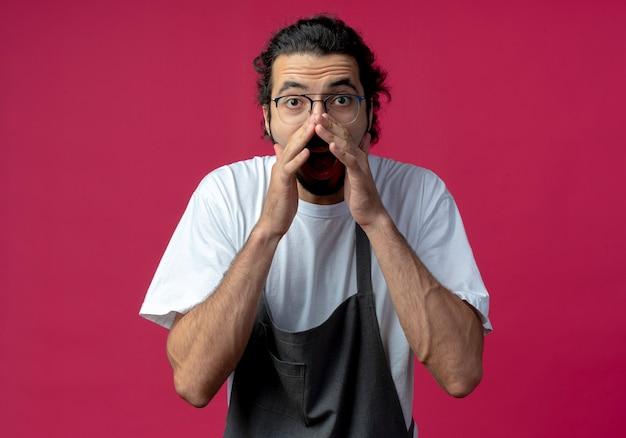 Beeindruckter junger kaukasischer männlicher friseur, der brille und welliges haarband in uniform trägt, die etwas an der kamera lokalisiert auf purpurrotem hintergrund flüstert