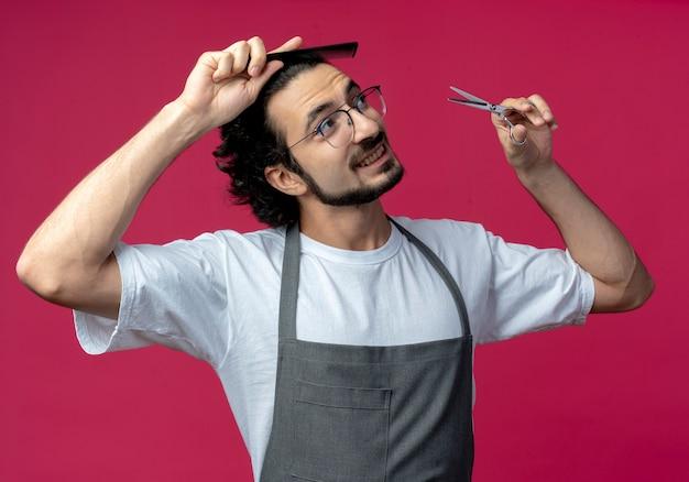 Beeindruckter junger kaukasischer männlicher friseur, der brille und welliges haarband in uniform trägt, die sein haar kämmt und schere hält, die seite lokal auf purpurrotem hintergrund betrachtet