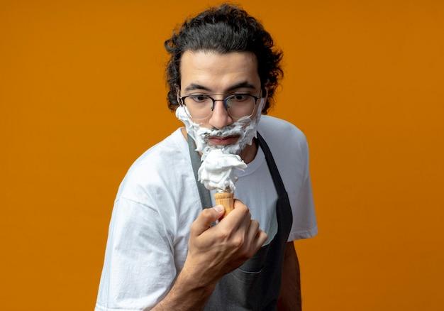 Beeindruckter junger kaukasischer männlicher friseur, der eine brille und ein welliges haarband in uniform trägt und einen rasierpinsel mit rasierschaum auf seinem gesicht betrachtet