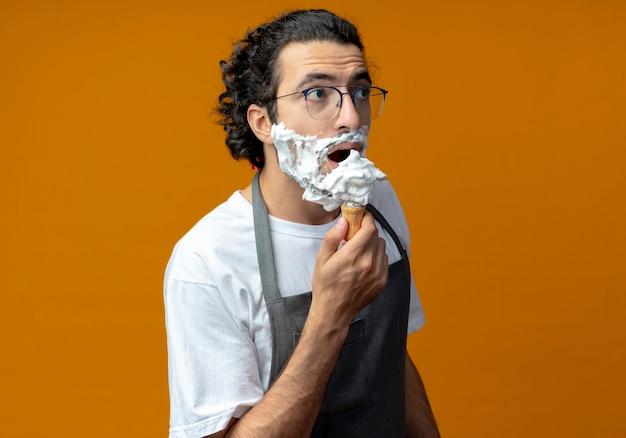 Beeindruckter junger kaukasischer männlicher friseur mit brille und welligem haarband in uniform, der einen rasierpinsel in der nähe des mundes mit rasierschaum auf seinem bart hält, der gerade aussieht