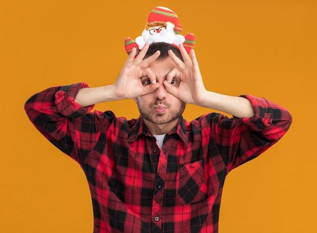 Beeindruckter junger kaukasischer mann, der das weihnachtsmann-stirnband trägt, das kamera betrachtet, die blickgeste unter verwendung der hände als fernglas mit gespitzten lippen lokalisiert auf orangeem hintergrund tut
