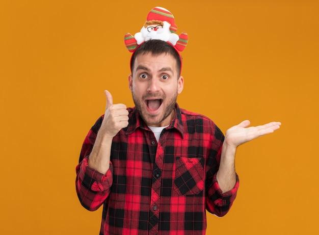 Beeindruckter junger kaukasischer mann, der das weihnachtsmann-stirnband trägt, das kamera betrachtet, die daumen oben und leere hand lokalisiert auf orange hintergrund zeigt