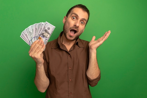 Beeindruckter junger kaukasischer mann, der geld hält, das leere hand lokalisiert auf grüner wand mit kopienraum zeigt