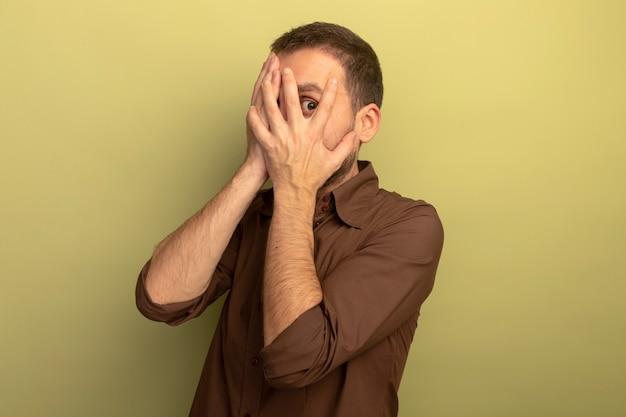 Beeindruckter junger kaukasischer mann, der hände auf gesicht setzt, das kamera durch finger lokalisiert auf olivgrünem hintergrund mit kopienraum betrachtet