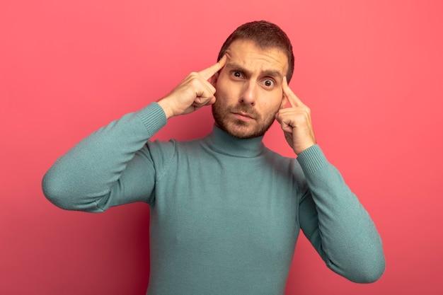 Beeindruckter junger kaukasischer mann, der kamera betrachtet, die denkgestik lokalisiert auf purpurrotem hintergrund betrachtet