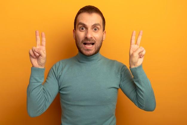 Beeindruckter junger kaukasischer mann, der kamera betrachtet, die friedenszeichen lokalisiert auf orange hintergrund tut