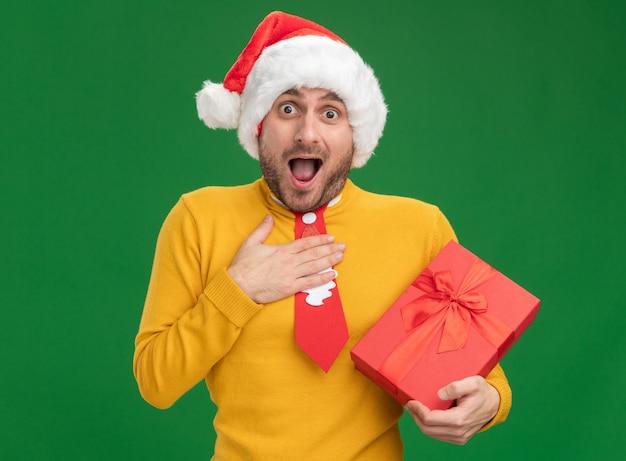 Beeindruckter junger kaukasischer mann, der weihnachtshut und krawatte hält, die geschenkpackung hält, die hand auf brust hält, die kamera lokalisiert auf grünem hintergrund betrachtet