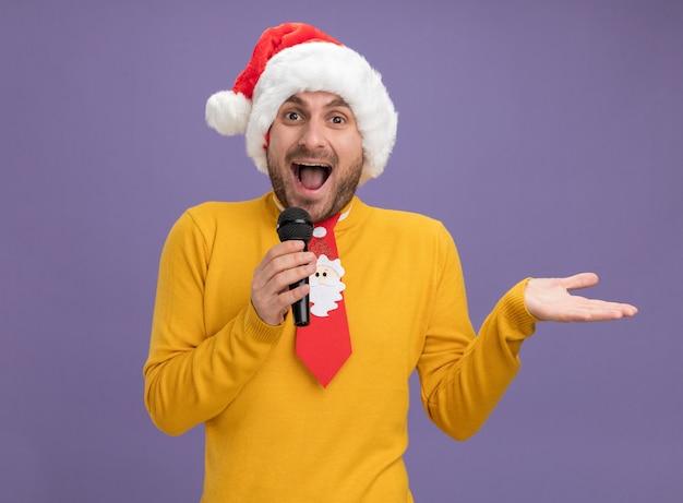 Beeindruckter junger kaukasischer mann, der weihnachtshut und krawatte hält, die mikrofon betrachten kamera, die leere hand lokalisiert auf lila hintergrund betrachtet