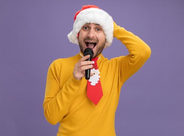 Beeindruckter junger kaukasischer mann, der weihnachtshut und krawatte hält mikrofon nahe mund betrachtet kamera betrachtet hand auf kopf lokalisiert auf lila hintergrund