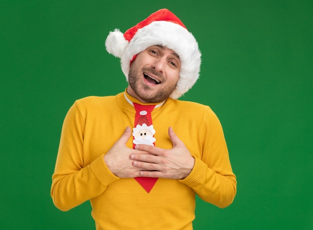 Beeindruckter junger kaukasischer mann, der weihnachtshut und krawatte trägt und kamera betrachtet, die dankesgeste lokalisiert auf grünem hintergrund tut