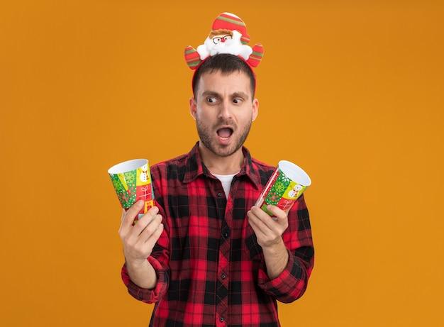 Beeindruckter junger kaukasischer mann, der weihnachtsmann-stirnband hält, das plastikweihnachtsbecher hält, die einen von ihnen lokalisiert auf orangefarbenem hintergrund betrachten