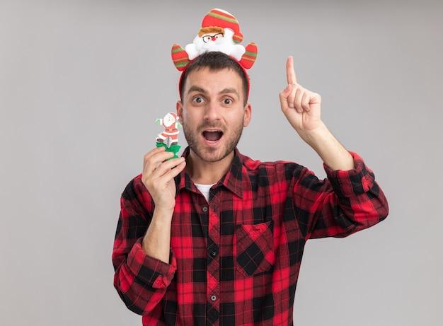 Beeindruckter junger kaukasischer mann, der weihnachtsmann-stirnband hält schneemann-weihnachtsspielzeug, das kamera zeigt, die oben auf weißem hintergrund zeigt