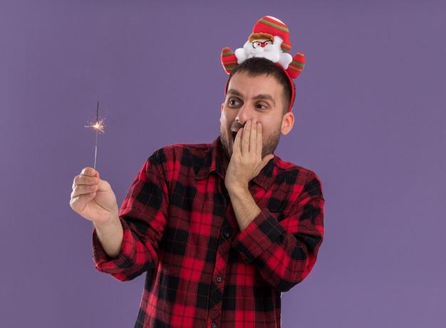 Beeindruckter junger kaukasischer mann, der weihnachtsmann-stirnband hält und feiertagswunderkerze hält, die hand auf gesicht lokalisiert auf lila hintergrund hält