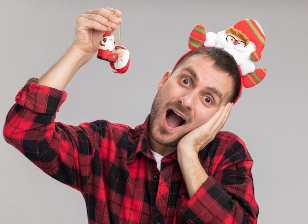 Beeindruckter junger kaukasischer mann, der weihnachtsmann-stirnband trägt, das weihnachtsmann-verzierungen des weihnachtsmanns anhebend betrachtet kamera hält hand auf gesicht lokalisiert auf weißem hintergrund