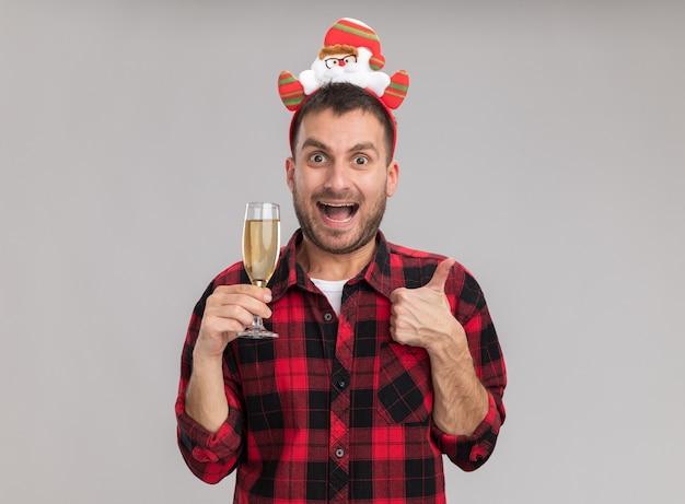 Beeindruckter junger kaukasischer mann, der weihnachtsstirnband hält, das glas champagner betrachtet kamera betrachtet daumen oben auf weißem hintergrund