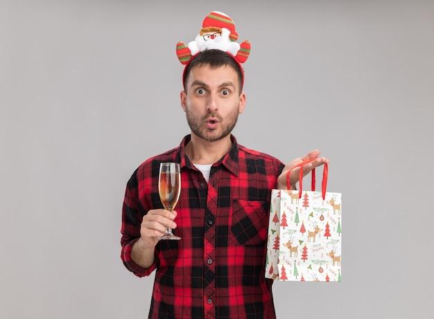 Beeindruckter junger kaukasischer mann, der weihnachtsstirnband hält weihnachtsgeschenkbeutel und glas champagner betrachtet kamera betrachtet auf weißem hintergrund