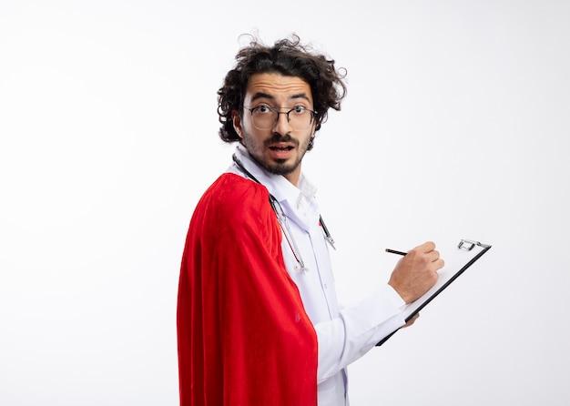 Beeindruckter junger kaukasischer superheldenmann in der optischen brille, die arztuniform mit rotem umhang und mit stethoskop um hals trägt, steht seitlich und schreibt in zwischenablage mit bleistift