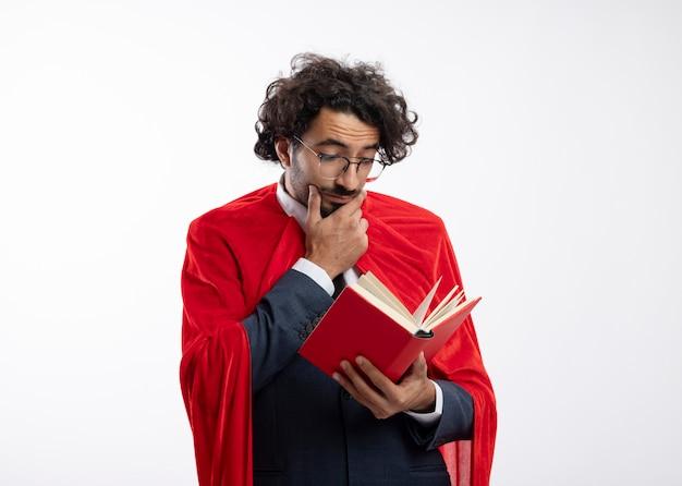 Beeindruckter junger kaukasischer superheldenmann in optischer brille, der anzug mit rotem mantel trägt, legt hand auf kinn und liest buch