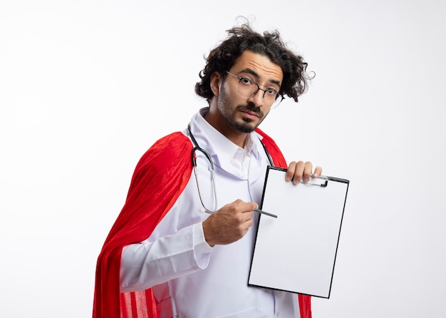 Beeindruckter junger kaukasischer superheldenmann in optischer brille, die arztuniform mit rotem umhang und mit stethoskop um hals hält und zeigt auf zwischenablage mit bleistift mit kopierraum