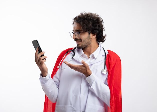 Beeindruckter junger kaukasischer superheldenmann in optischer brille in arztuniform mit rotem mantel und mit stethoskop um den hals sieht aus und zeigt auf das telefon
