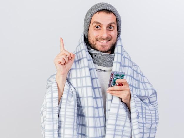Beeindruckter junger kranker mann, der wintermütze und schal trägt, die in karierte haltepillen eingewickelt werden