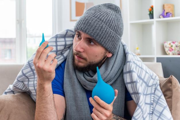Beeindruckter junger kranker mann mit schal und wintermütze, der auf dem sofa im wohnzimmer sitzt und in eine decke gehüllt ist, die einläufe hält und einen anschaut