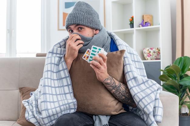 Beeindruckter junger kranker mann mit schal und wintermütze, der in decke gewickelt auf einem sofa im wohnzimmer sitzt und ein kissen hält, das mund und nase bedeckt, mit einem schal, der nach oben schaut und pillenpackungen hält