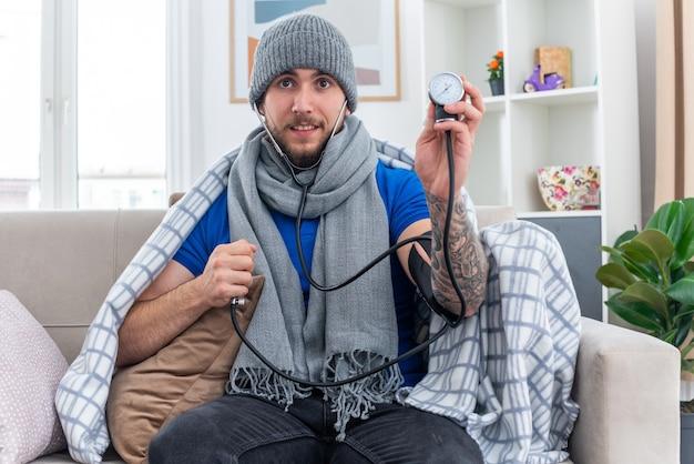 Beeindruckter junger kranker mann mit schal und wintermütze mit in decke gewickeltem stethoskop, der auf dem sofa im wohnzimmer sitzt und ein blutdruckmessgerät zeigt