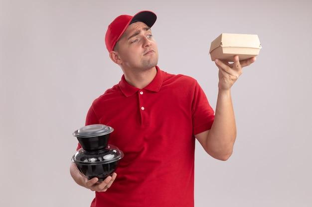 Beeindruckter junger lieferbote, der uniform mit kappe hält, die lebensmittelbehälter hält und papiernahrungsmittelpaket in seiner hand lokalisiert auf weißer wand betrachtet